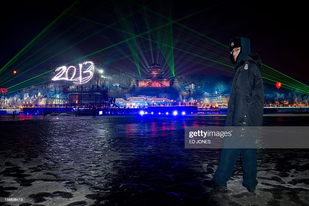 A security guard stands on a frozen lake as a light show illuminates the Summer Palace during a new year count-down event in Beijing on December 31, 2013. AFP PHOTO / Ed Jones