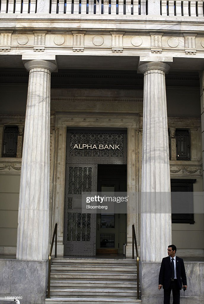 A security guard stands outside the entrance to the offices of Alpha Bank AE in Athens, Greece, on Tuesday, Jan. 22, 2013. Euro-area finance ministers blessed the next disbursement of emergency aid for Greece, highlighting the goodwill that led to the unblocking of loans last month for Prime Minister Antonis Samaras's government. Photographer: Kostas Tsironis/Bloomberg via Getty Images