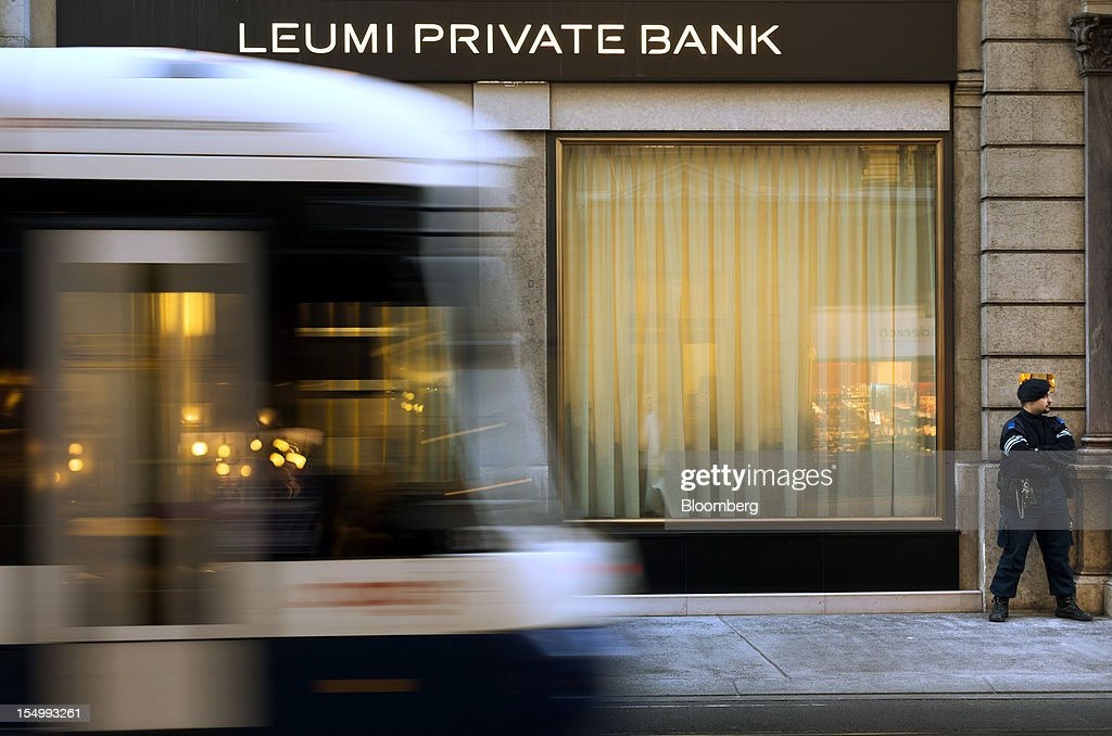 A security guard stands outside the Leumi Private bank, a subsidiary of Bank Leumi Le-Israel, in Geneva, Switzerland, on Monday, Oct. 29, 2012. Geneva's banks employed 502 fewer people at the end of June compared with a year earlier as foreign wealth managers cut jobs and shifted employees to other locations, a survey by the city's financial lobby group shows. Photographer: Valentin Flauraud/Bloomberg via Getty Images