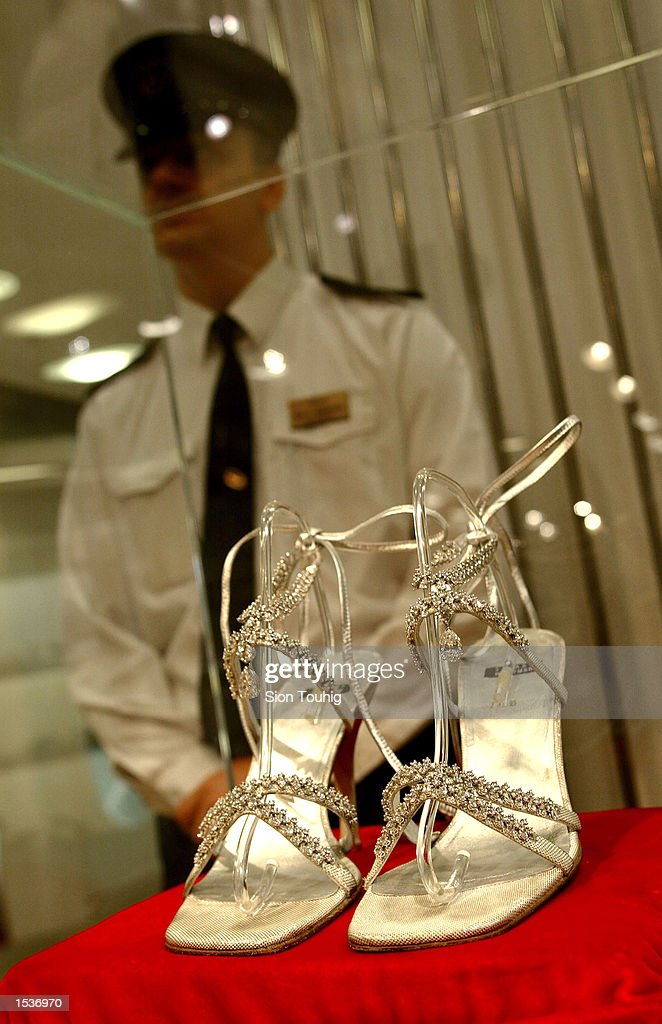 A security guard stands watch over a pair of Stuart Weitzman $1M diamond and platinum shoes April 29, 2002 in London. The shoes, worn by model Laura Elena Harring at this year's Oscars, are covered with 464 diamonds and are the most expensive shoes in the world. The shoes are going on sale at Harrod's department store and the proceeds will go to childrens'' charities.