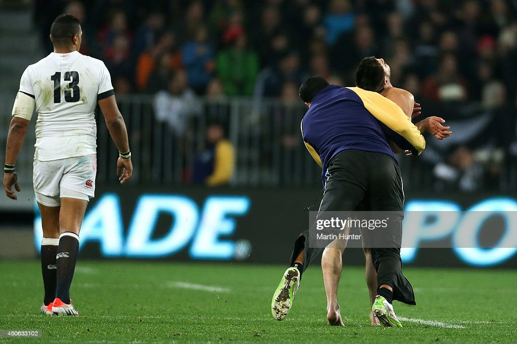 A security guard tackles a streaker as Luther Burrell of England looks on during the International Test Match between the New Zealand All Blacks and England at Forsyth Barr Stadium on June 14, 2014 in Dunedin, New Zealand.