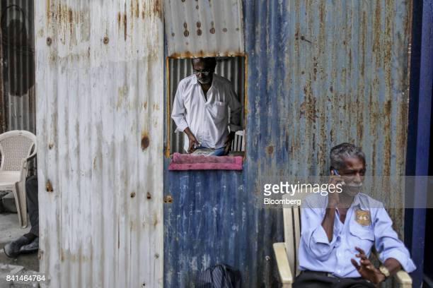 A security guard talks on mobile phone at the Mumbai Metro Rail Corp casting yard in Mumbai India on Monday Aug 28 2017 The expanding mega city's...