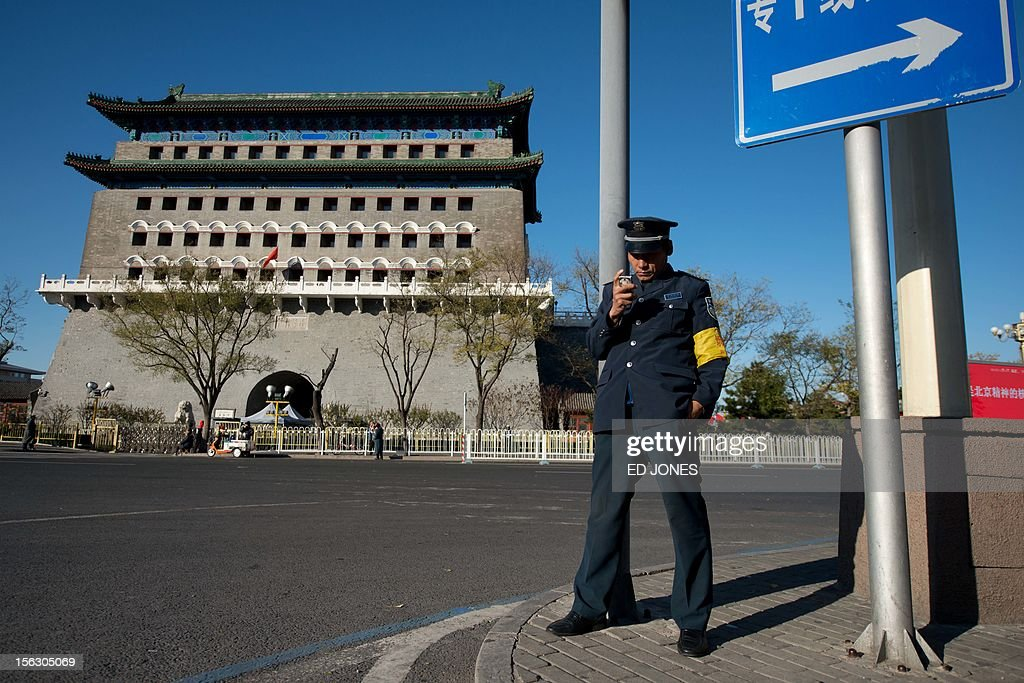 A security guard uses a mobile phone as he stands before the Qianmen gate on Tiananmen Square in Beijing on November 13, 2012. China's Communist Party will on November 15 unveil the new set of top leaders who will run the country for the next decade, one day after its week-long congress ends. AFP PHOTO / Ed Jones