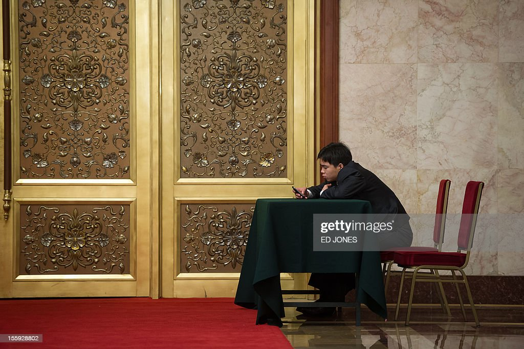 A security guard uses his mobile phone as he sits inside the Great Hall of the People in Beijing on November 9, 2012. The week-long congress, held every five years, will end with a transition of power to Vice President Xi Jinping, who will govern for the coming decade amid growing pressure for reform of the communist regime's iron-clad grip on power. AFP PHOTO / Ed Jones