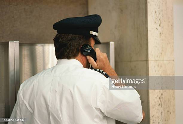 Security guard using telephone, rear view