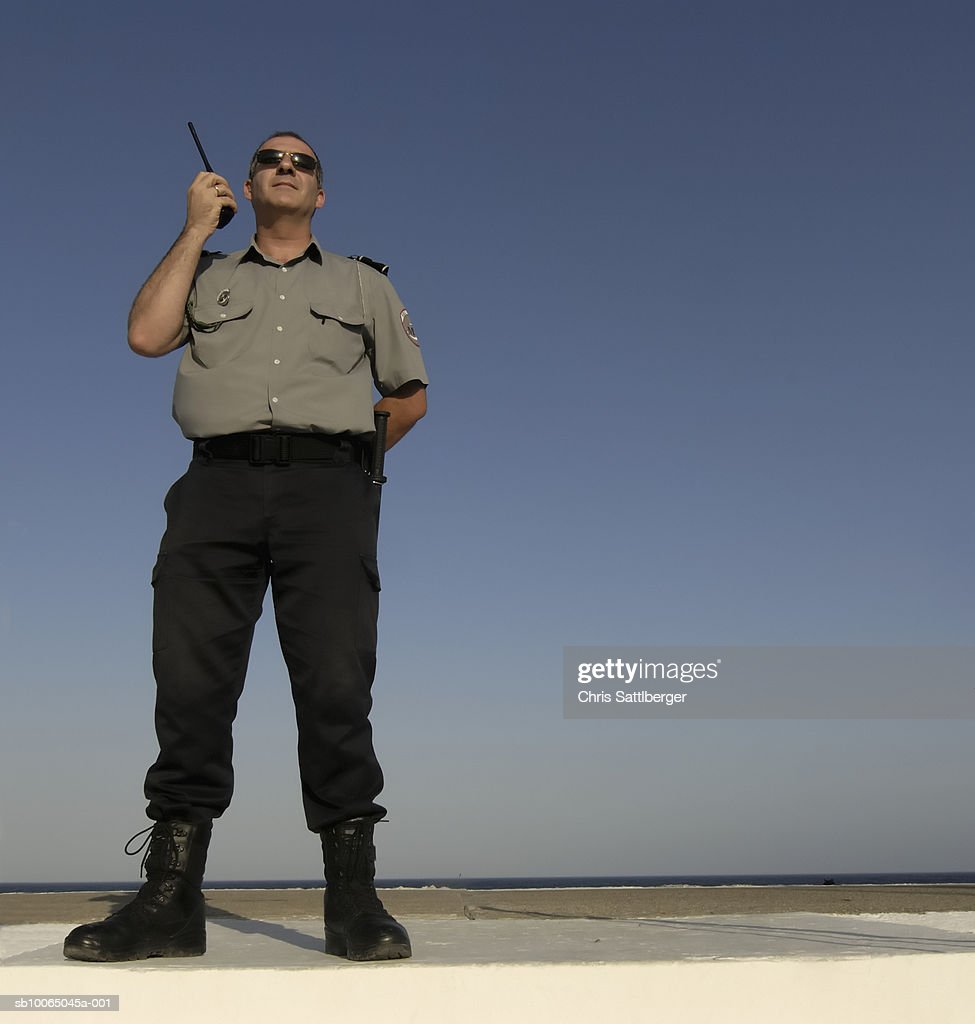 Security guard using walkie-talkie, outdoors, low angle view : Stock Photo