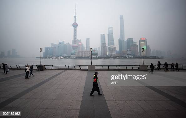 TOPSHOT A security guard walks at the bund near the Huangpu river across the Pudong New Financial district in Shanghai on January 18 2016 China...