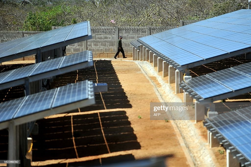 A security guard walks during the inauguration of a photovoltaic power plant in Diriamba, 42 km from Managua on February 21, 2013. The power plant, that includes 5880 solar photovoltaic panels and has a capacity of one megawatt, was built with a donation of USD 11,9 millons from Japan and will provide power to 1,100 homes. AFP PHOTO/Hector RETAMAL