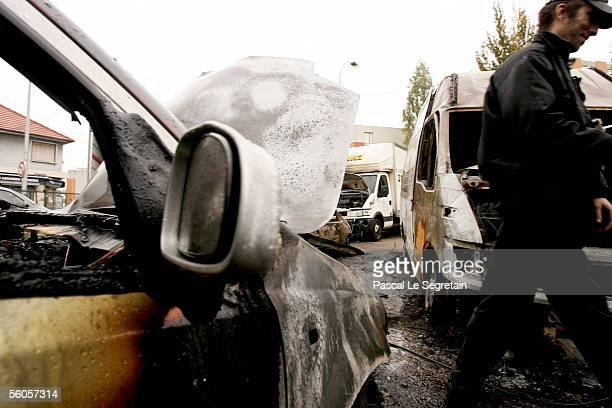 A security guard walks past burned vehicles at Hertz rental car company on November 2 2005 in AulnaysousBois outside Paris France Dozens of vehicles...
