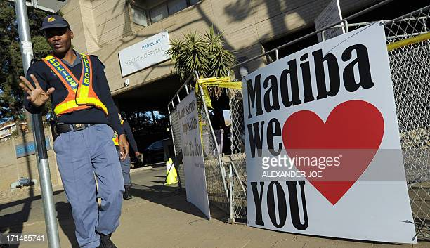 A security guard walks past signs wishing well and quoting former South African president Nelson Mandela on June 25 2013 outside of the Mediclinic...