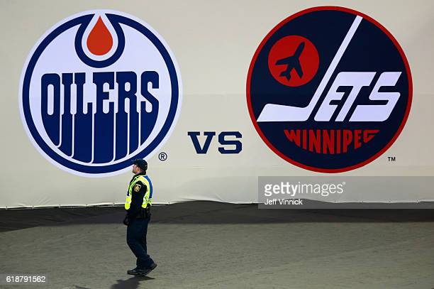 A security guard walks past the logo's of the Edmonton Oilers and the Winnipeg Jets during the 2016 Tim Hortons NHL Heritage Classic at Investors...