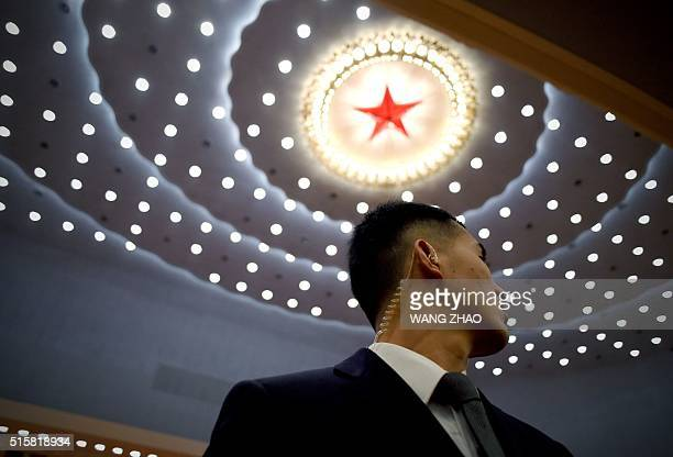 A security guard watches during the closing session of the National People's Congress in the Great Hall of the People in Beijing on March 16 2016 The...