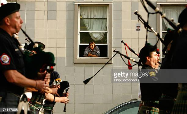 A security guard watches from a window as hundreds of law enforcement bagpipe players and honor guards make their way down 6th Street NW during the...