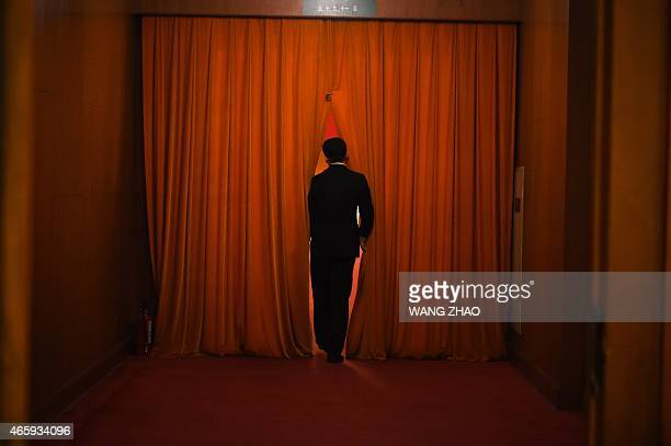 A security guard watches through the curtain during the 3rd plenary session of the third session of the 12th National People's Congress at the Great...
