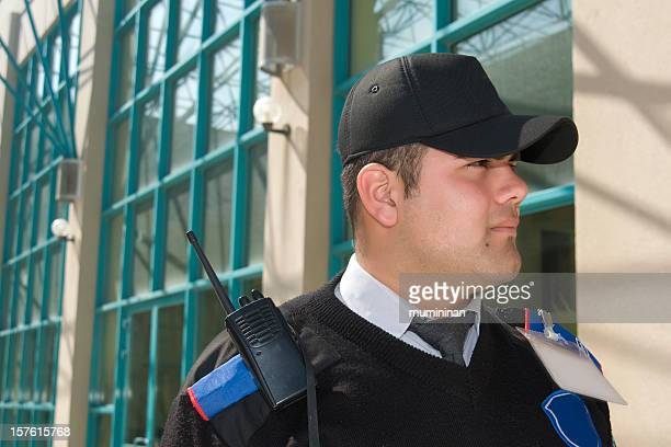 Security guard wearing a ball cap in front of a building