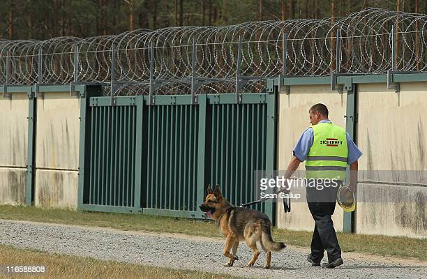 A security guard with a dog patrols the barbedwire perimieter at the Gorleben salt mines on June 16 2011 in Gorleben Germany German authorities are...