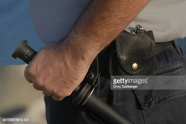 Security guard with baton and handcuffs in holster, close-up