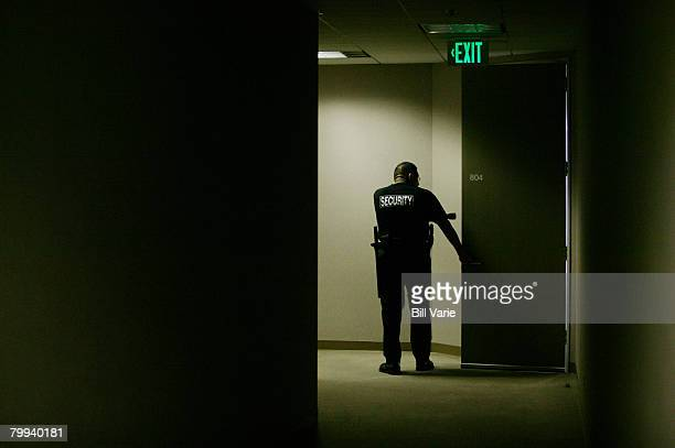 Security Guard with Flashlight Checking Doorway