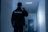 Rear view of security guard with flashlight in building corridor