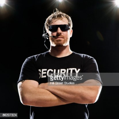 Security guard with headset posing with arms crossed