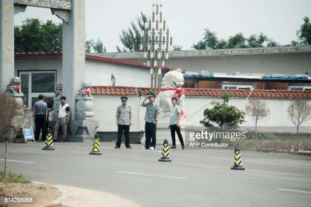 Security guards and plainclothes police officer stand guard at the entrance of Xihe funeral parlor and cemetary where Liu Xiaobo's body is believed...