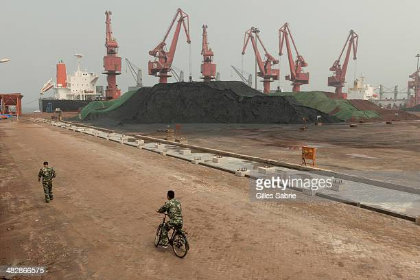 CAOFEIDIAN TANGSHAN HEBEI CHINA Security guards by Cafofeidian harbor where coal and iron ore are unloaded to feed Shougang steel mill the only major...
