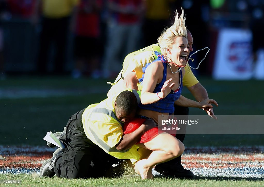 Security guards chase a fan wearing a costume after she ran on the pitch during the Cup Final match between Fiji and New Zealand during the USA...