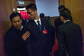 Security guards check delegates at an entrance during the 3rd plenary session of the third session of the 12th National People's Congress at the...