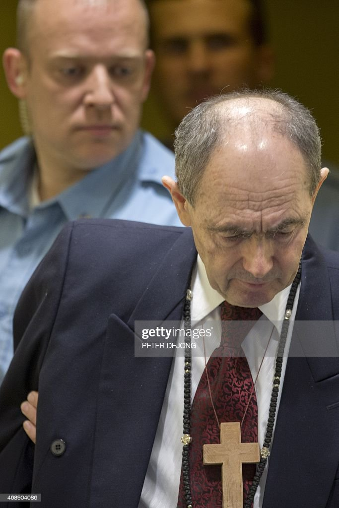 UN security guards escort Bosnian Serb general <a gi-track='captionPersonalityLinkClicked' href=/galleries/search?phrase=Zdravko+Tolimir&family=editorial&specificpeople=4311362 ng-click='$event.stopPropagation()'>Zdravko Tolimir</a> as he arrives at the courtroom of UN's Yugoslav war crimes court in The Hague, on April 8, 2015. The UN's Yugoslav war crimes court found Bosnian Serb general <a gi-track='captionPersonalityLinkClicked' href=/galleries/search?phrase=Zdravko+Tolimir&family=editorial&specificpeople=4311362 ng-click='$event.stopPropagation()'>Zdravko Tolimir</a> guilty of genocide for his role in the 1995 Srebrenica massacre, Europe's worst atrocity since World War II, and sentenced him to life in jail.
