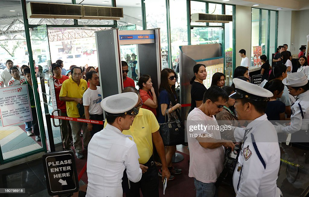 Security guards frisk shoppers as they enter a mall in Manila on February 6, 2013, as part of heightened security after recent attacks at shopping centres. Police have stepped up their visibility and security in response to recent attacks in popular Manila shopping malls, including the ransacking of a mall jewellery store on January 26.