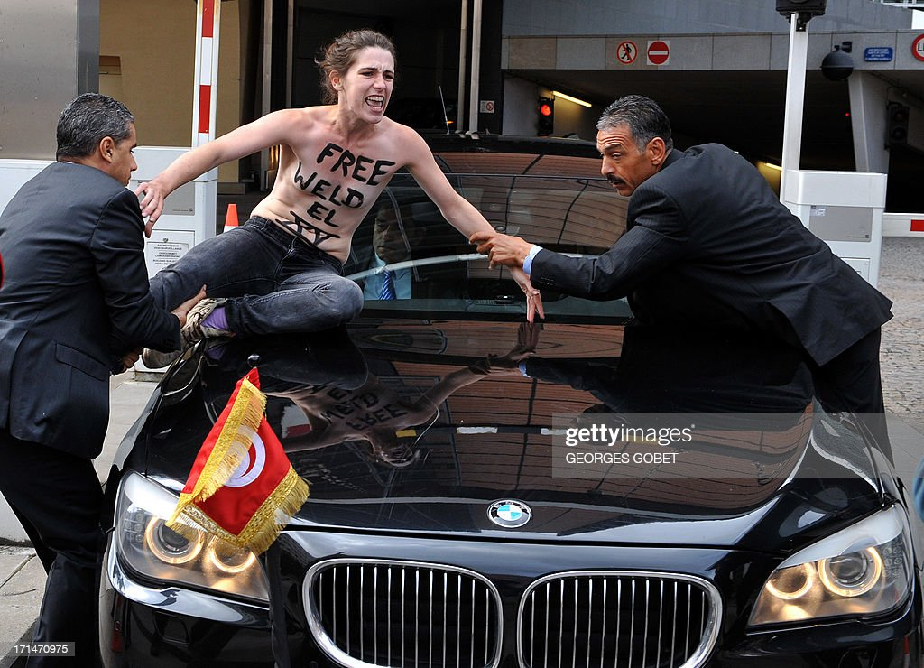 Security guards grab a Femen activist as she tried to stop the car of Tunisian Prime Minister from leaving the EU commission building after his working session with European Commission President on June 25, 2013 at the EU headquarters in Brussels.