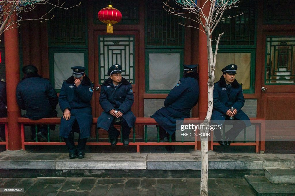 Security guards have a break at Baiyunguan Temple during Lunar New Year celebrations in Beijing on February 11, 2016. Millions of Chinese are celebrating the 'Spring Festival', the most important holiday on the Chinese calendar, which this year marks the beginning of the Year of the Monkey. AFP PHOTO / FRED DUFOUR / AFP / FRED DUFOUR