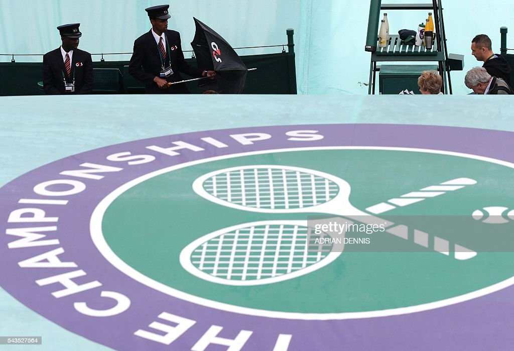 Security guards hold umbrellas as rain halts the start of the third day of the 2016 Wimbledon Championships at The All England Lawn Tennis Club in Wimbledon, southwest London, on June 29, 2016. / AFP / ADRIAN