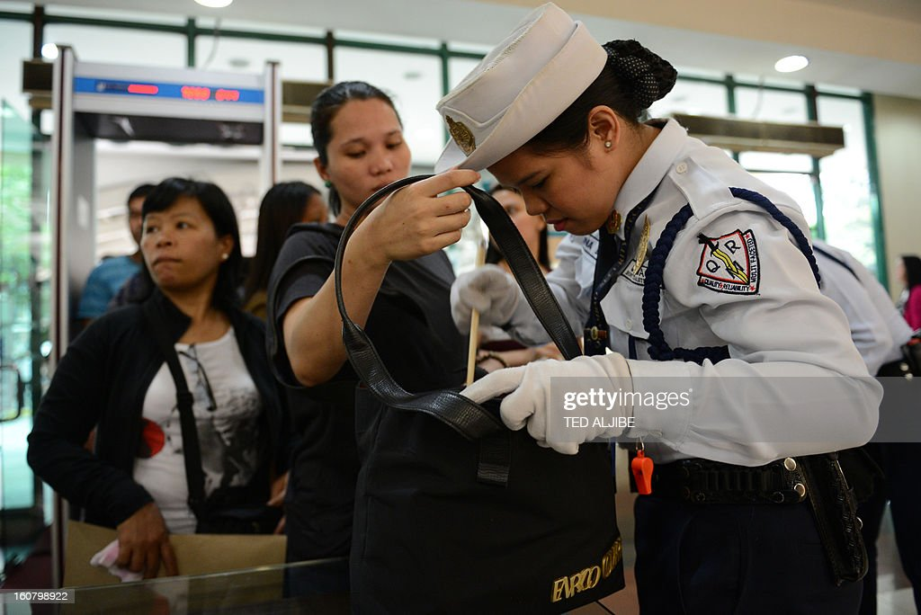 Security guards inspect shoppers' bags at the entrance of a mall in Manila on February 6, 2013, as part of heightened security after recent attacks at shopping centres. Police have stepped up their visibility and security in response to recent attacks in popular Manila shopping malls, including the ransacking of a mall jewellery store on January 26. AFP PHOTO/TED ALJIBE