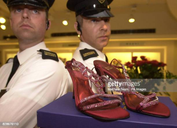 Security guards keep a watchful eye over the pair of ruby and platinum slippers in the shoe department at London's Harrods store The world's most...