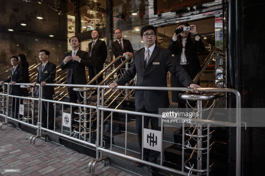 Security guards keep vigil at the entrance of a building owned by Asia's richest man Li Ka-shing as dockers asking for an increase in pay and better working conditions march in Hong Kong on April 18, 2013. The dockers who pledged to escalate their demonstrations have begun protesting outside Cheung Kong Centre, the headquarters Li Ka-shing whose firms control about 70 percent of the in the city's port traffic. AFP PHOTO / Philippe Lopez