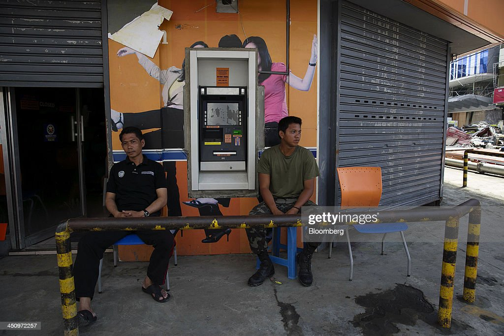 Security guards keep watch outside a Union Bank of the Philippines (UnionBank) automated teller machine (ATM) in Tacloban, the Philippines, on Monday, Nov. 18, 2013. Super Typhoon Haiyan slammed into the central Philippines on Nov. 8, knocking down most buildings, killing thousands, displacing 4 million people and affecting more than 10 million. Photographer: Paula Bronstein/Bloomberg via Getty Images