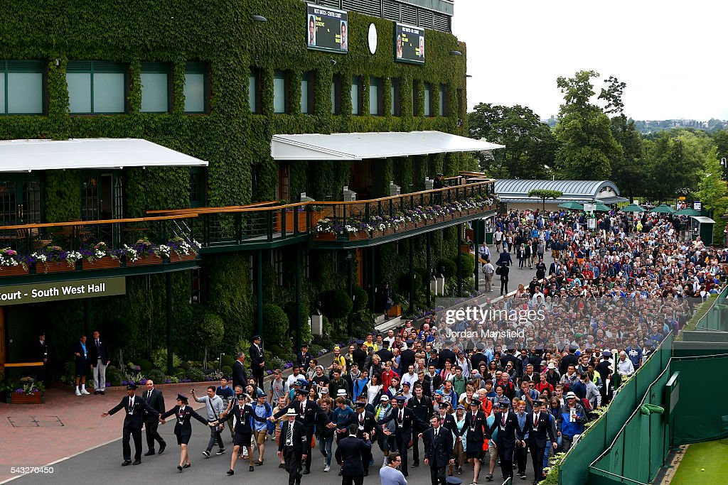 Security guards lead spectators in as gates open ahead of the start of day one of the Wimbledon Lawn Tennis Championships at the All England Lawn Tennis and Croquet Club on June 26, 2016 in London, England.