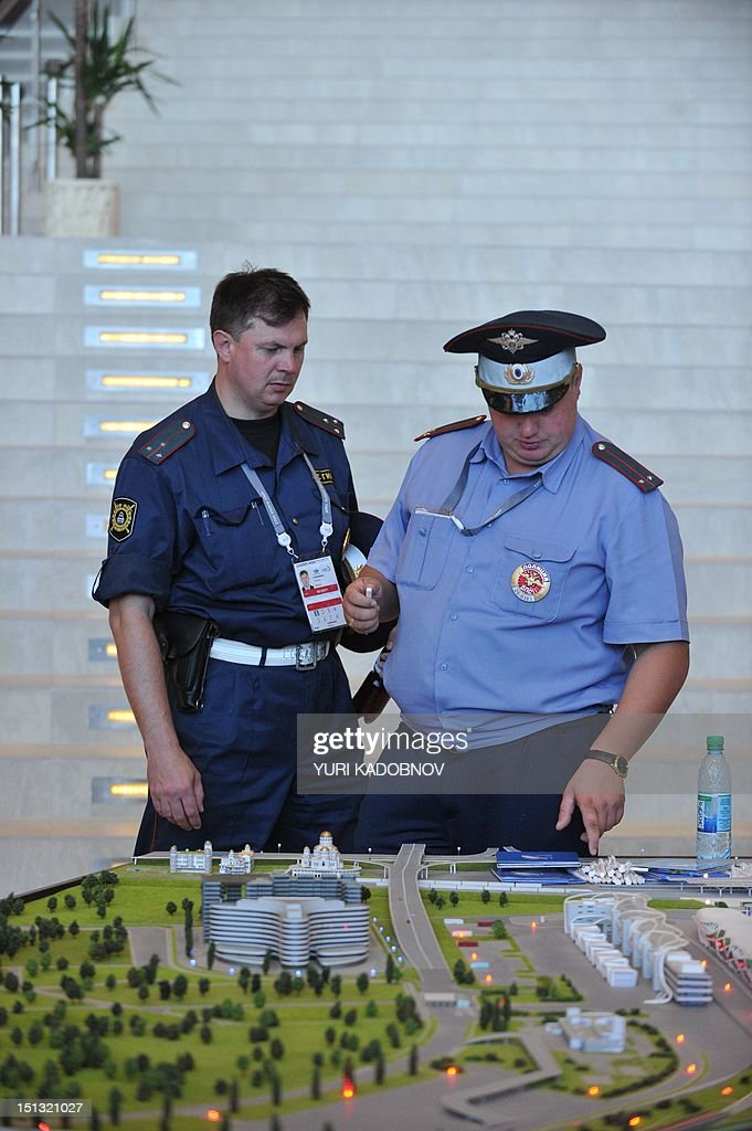 Security guards look at a model display on the upcoming 2014 Winter Olympics in Sochi, during the Asia-Pacific Economic Cooperation (APEC) summit in Vladivostok on September 6, 2012. Russia, which hosts its first annual Vladivostok APEC summit this week, is seeking to assert its presence in the fast-growing region during troubled European economic times. APEC leaders' summit in Russia's far eastern port city of Vladivostok will take place on September 8 and 9. AFP PHOTO / YURI KADOBNOV