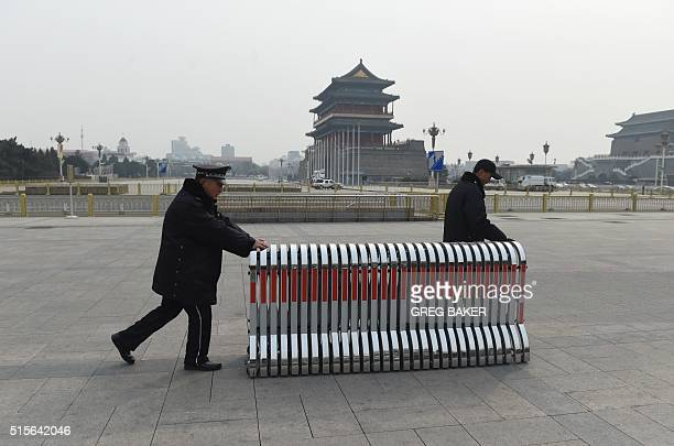 Security guards move a security barrier near the Great Hall of the People where meetings of the ongoing National People's Congress are being held in...