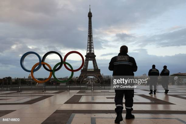 Security guards patrol at sunrise by the Olympic rings installed on the Esplanade du Trocadero near the Eiffel tower following the Paris' nomination...