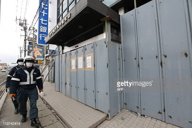 Security guards patrol outside bank offices that have their front blocked with steel plates in Ishinomaki MNiyagi prefecture on March 24 2011 The...