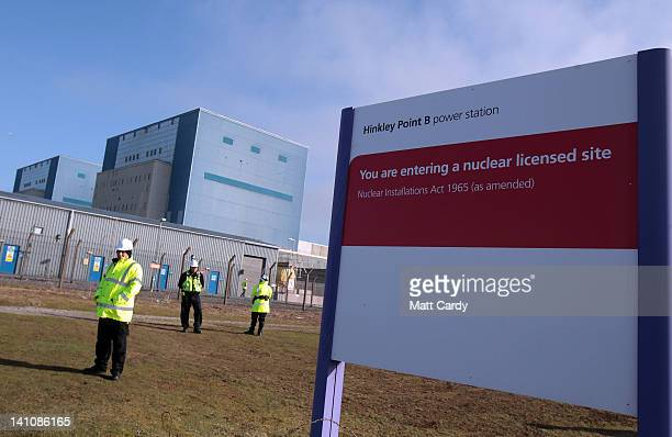 Security guards patrol the grounds of the Hinkley Point nuclear power station as demonstrators gather to mark the first anniversary of the Fukushima...