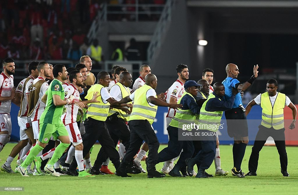 Security guards protect referee Rajindraparsad Seechurn from Tunisia's players at the end of the 2015 African Cup of Nations quarterfinal football...