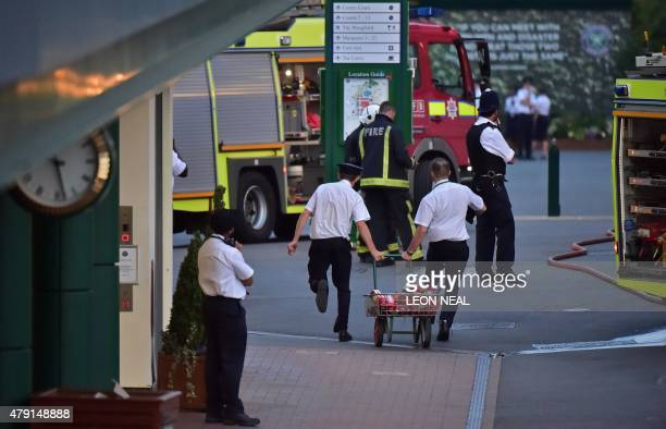 G4S security guards pull a trolley loaded with fire extinguishers as Fire engines and Police vans stand parked outside Centre Court following a fire...