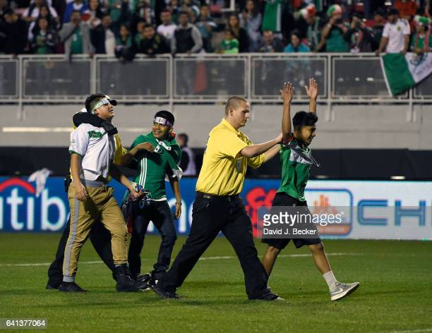 Security guards remove fans who ran onto the field after Mexico defeated Iceland 10 in an exhibition match at Sam Boyd Stadium on February 8 2017 in...