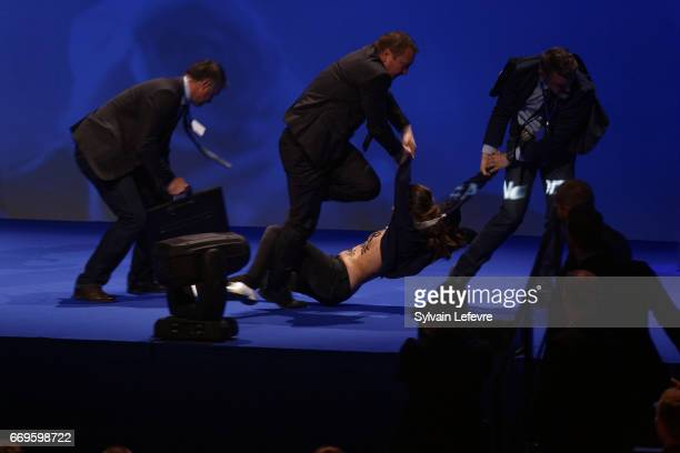 Security guards remove the Femen protestor who attempted to storm the stage during french presidential farright candidate Marine Le Pen speech during...