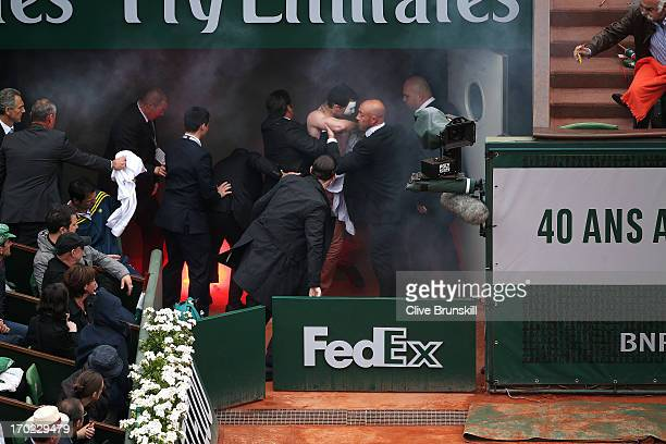 Security guards restrain a protester after he lit a flare and ran on court before the start of a game in the Men's Singles final match between Rafael...