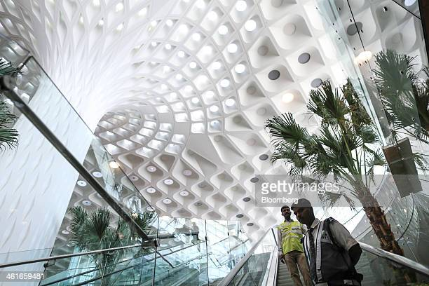 Security guards ride on an escalator inside the newly built Terminal 2 of the Chhatrapati Shivaji International Airport operated by GVK Power...