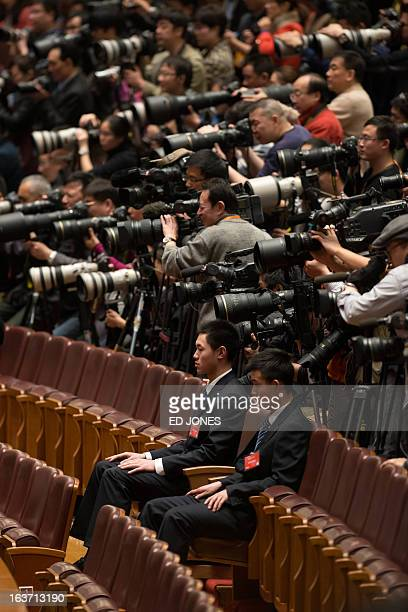 Security guards sit before journalists during a session of the National People's Congress at the Great Hall of the People in Beijing on March 15 2013...